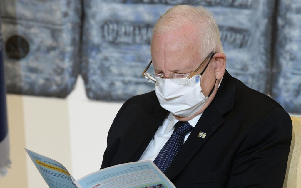President Reuven Rivlin reads a report on the state of young people at risk during the coronavirus pandemic prepared by the Elem organization on July 6, 2020. (Mark Neyman/GPO)