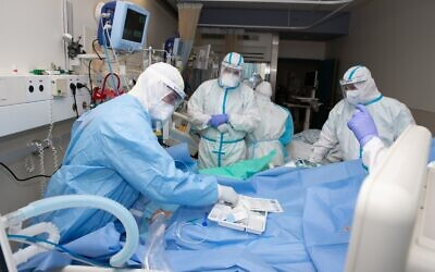 Medical staff treat a coronavirus patient at Shaare Zedek Medical Center in Jerusalem (Tal Cheres)