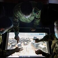 Illustrative. Soldiers from the Military Intelligence Unit 9900, which specializes in visual intelligence, use a map of a military base in southern Israel in an undated photograph. (Israel Defense Forces)