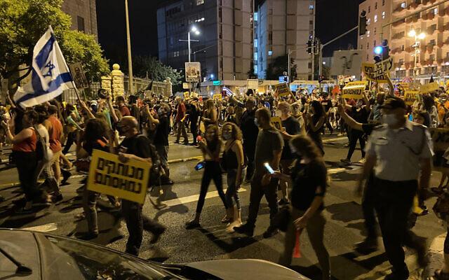 Demonstrators calling for the resignation of Prime Minister Benjamin Netanyahu march along Jerusalem's Keren Hayesod street on July 18, 2020 (ToI staff)