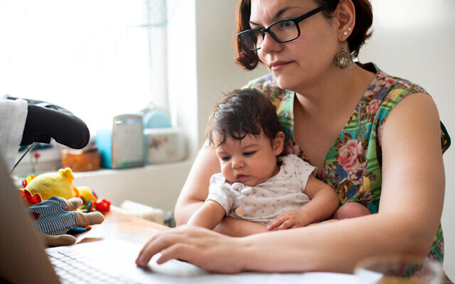 Working mom with baby in a lap (StockRocket; iStock by Getty Images)