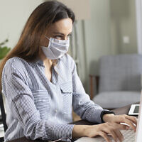 Illustrative: A woman wearing a mask works in the office on a laptop (eternalcreative; iStock by Getty Images)