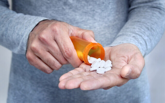 Illustrative: A man holds a bottle of pills (outline205; iStock by Getty Images)