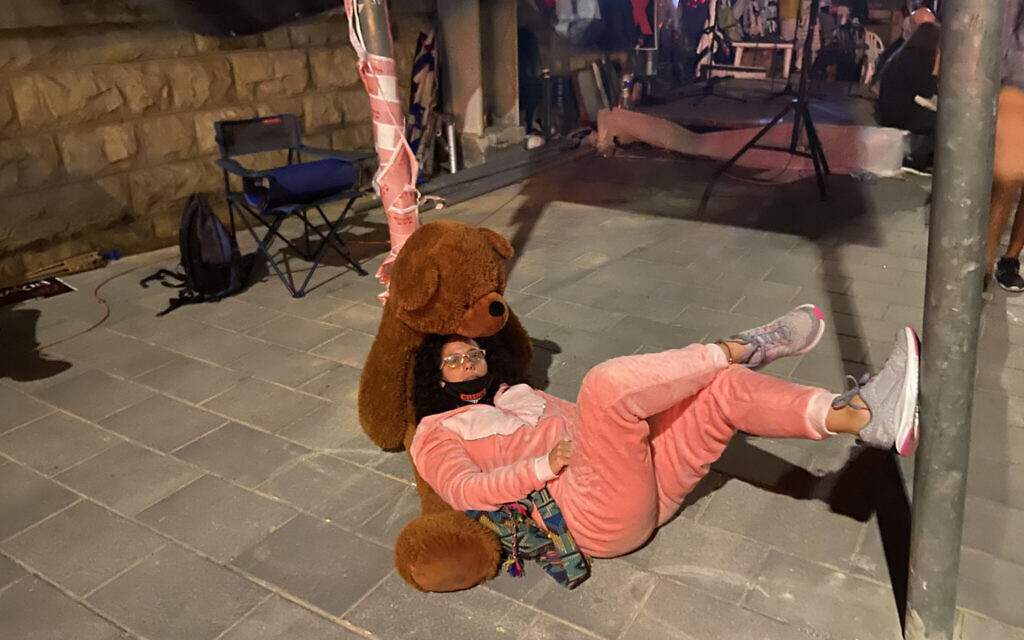 Mirav Ben-Uziel, in her pink pajama onesies and with her teddy bear, outside the Prime Minister's Residence in Jerusalem, July 16, 2020 (Anat Peled)