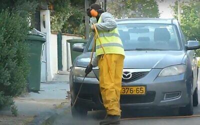 Spraying an Israeli street with weedkiller. (YouTube screenshot)
