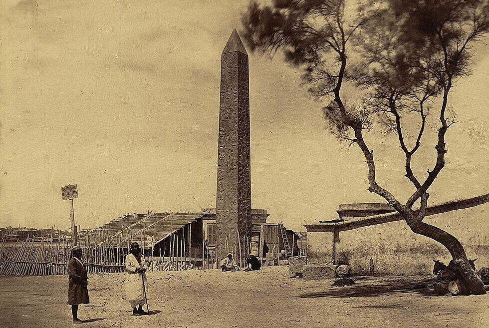 Cleopatra's Needle, an obelisk, towers above small buildings, local residents and a single tree in Alexandria, Egypt, circa 1856-1860, photograph by Frank Mason Good. (Library of Congress)