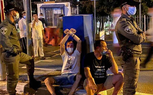 Protesters sitting by police as water cannons dispersed demonstrators at anti-Netanyahu rally on Agron Street (Anat Peled/Times of Israel)