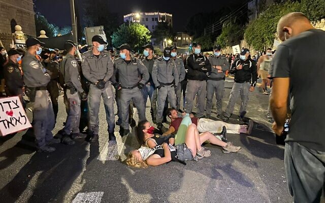 Protesters lie down in front of riot police on Ben Maimon Street outside the Prime Minister's Residence in Jerusalem on Sunday, July 26, 2020. (Anat Peled/Times of Israel)