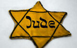 The yellow star, which Jews were forced to wear under Nazi rule, reads 'Jew', on display in a vitrine at the memorial place Wewelsburg in Bueren-Wewelsburg, Germany, 22 January 2015. (Caroline Seidel/picture alliance via Getty Images via JTA)