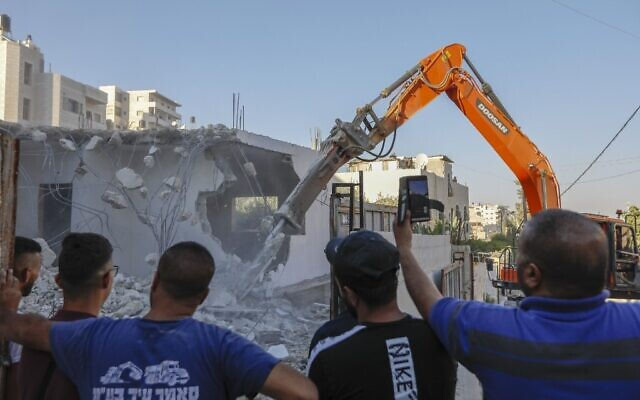 Relatives of the Shalalda family watch as an excavator hired by them demolishes their family home in Al-Tur in east Jerusalem on July 2, 2020 (AHMAD GHARABLI / AFP)