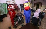 Disabled Gazan couple Nihad Jarboa, 37, (L) and his wife Zeinab, 35, sit on their wheelchairs as clients try on cartoon-inspired costumes stitched by them, at their home in the Rafah refugee camp in the southern Gaza Strip, on July 19, 2020. (Photo by SAID KHATIB / AFP)