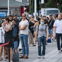 A man wearing a protective mask walks next to travellers as they queue up to board a boat at Stranvagen in Stockholm on July 27, 2020, during the novel coronavirus / COVID-19 pandemic. - Although the use of face masks has become taken for granted in many parts of the world, authorities of the Nordic countries (Sweden, Denmark, Norway, Finland and Iceland) and their more than 25 million inhabitants still defy the use of face masks to curb the spread of the virus. (Photo by Jonathan NACKSTRAND / AFP)