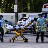 Medics transfer a patient on a stretcher from an ambulance outside of the emergency room at Coral Gables Hospital, where coronavirus patients are treated in Coral Gables, Florida, on July 30, 2020. (Chandan Khanna/AFP)
