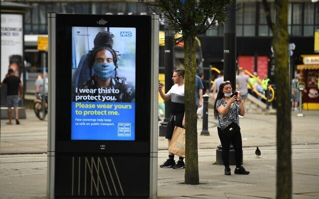 A large electronic billboard displays a message urging people to wear a face mask as a precuation against the transmission of the novel coronavirus, in Manchester, northwest England, on July 31, 2020 (Oli SCARFF / AFP)