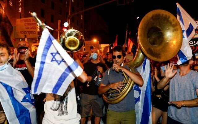 Protesters, mask-clad due to the COVID-19 coronavirus pandemic, gather around others playing brass instruments during a demonstration against the Israeli government near the Prime Minister's residence in Jerusalem on August 1, 2020. ( MENAHEM KAHANA / AFP)