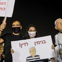 A protester wearing a face mask of Prime Minister Benjamin Netanyahu takes part in a demonstration against the government in Tel Aviv on August 1, 2020. (Jack Guez/AFP)