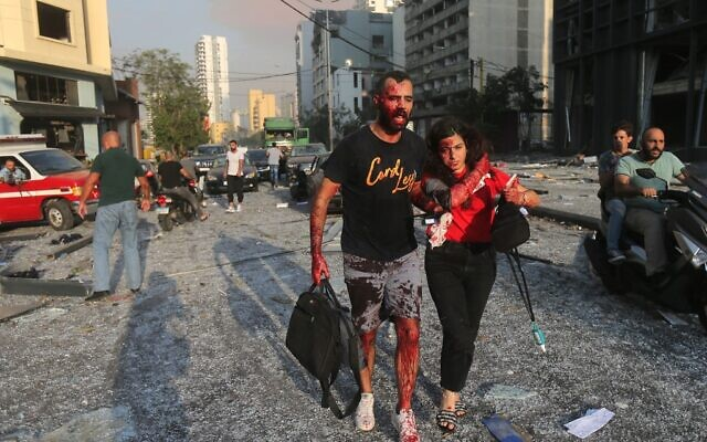 Wounded people walk near the site of an explosion at the port in the Lebanese capital Beirut on August 4, 2020 (STR / AFP)