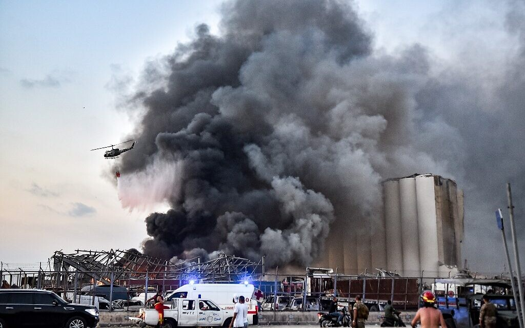 helicopter puts out a fire at the scene of an explosion at the port of Lebanon's capital Beirut on August 4, 2020. (STR / AFP)