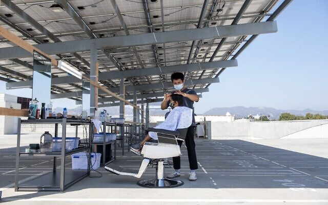 A stylist from Grey Matter LA cuts a young client's hair on a rooftop parking lot amid the coronavirus pandemic, August 4, 2020, in Los Angeles, California. (VALERIE MACON/AFP)