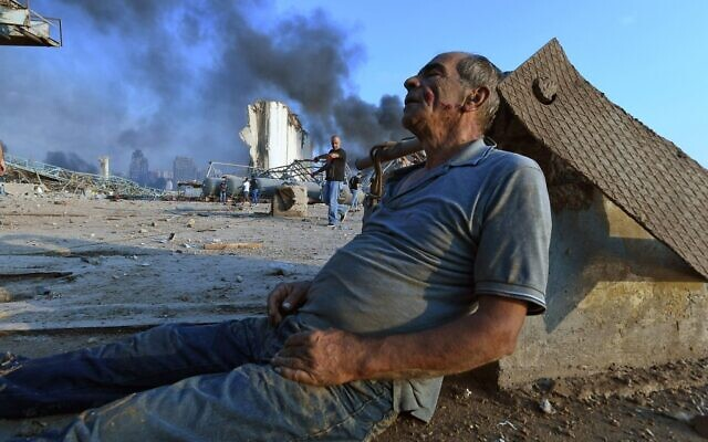 A wounded man sits on the ground waiting for aid at Beirut's port following a massive explosion that hit the heart of the Lebanese capital on August 4, 2020. (AFP)