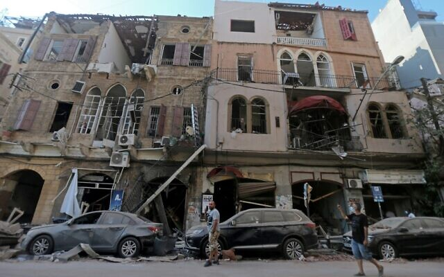 Pedestrians walks past damaged historic buildings on August 5, 2020 in Beirut's Gimmayzeh district which was heavily damaged by the previous day's powerful explosion that tore through Lebanon's capital, resulting from the ignition of a huge depot of ammonium nitrate at the city's main port. (Photo by STR / AFP)