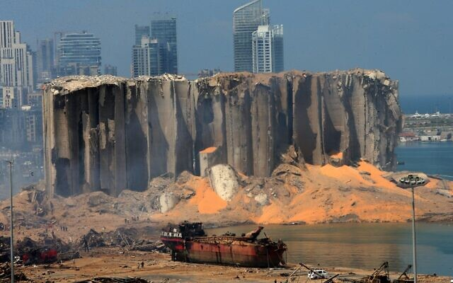 A picture taken on August 5, 2020 shows the damaged grain silo and a burnt boat at Beirut's harbour, one day after a powerful twin explosion tore through Lebanon's capital, resulting from the ignition of a huge depot of ammonium nitrate at the city's main port. (STR / AFP)