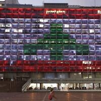 Illustrative: The Tel Aviv city hall is lit up in the colors of the Lebanese flag in solidarity with the victims of the Beirut port explosion, August 5, 2020. (Jack Guez/AFP)