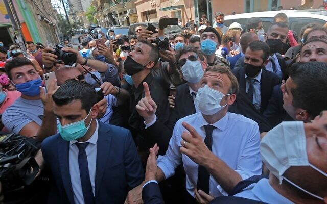 French President Emmanuel Macron chats with people as he visits Beirut's Gemmayzeh neighborhood which has suffered extensive damage due to a massive explosion in the Lebanese capital, on August, 6. 2020 (AFP)