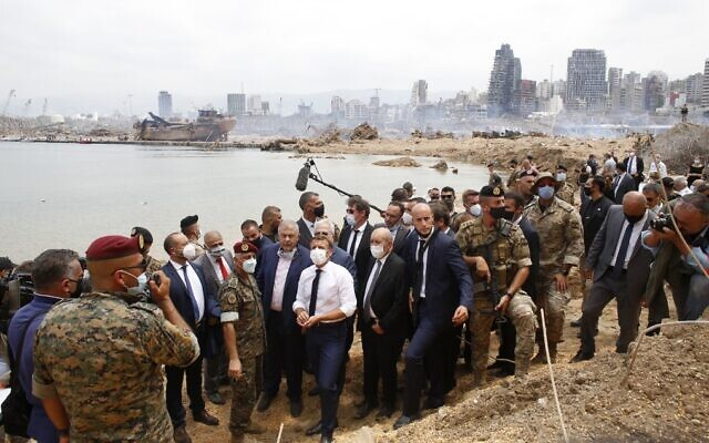French President Emmanuel Macron (C), flanked on his right by French Foreign Minister Jean-Yves Le Drian, visits the devastated site of the explosion at the Beirut port on August 6, 2020. (Thibault Camus/Pool/AFP)