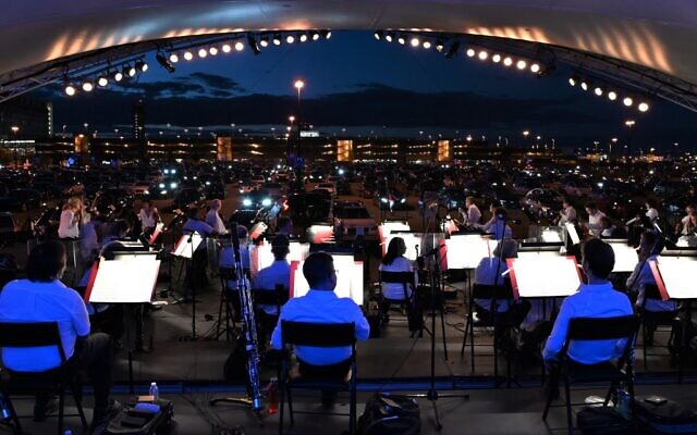 """The Montreal Symphony Orchestra performs in a parking lot at Montreal-Pierre Elliott Trudeau International Airport on August 5, 2020, during a socially-distanced """"drive-in"""" concert amid the COVID-19 outbreak. (Eric THOMAS/AFP)"""
