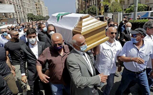 Members of the Lebanese Kataeb party carry the coffin of their party's secretary-general Nazar Najarian, killed by the explosion that hit the seaport of Beirut on August 4, during his funeral procession in the capital Beirut, on August 8, 2020. (ANWAR AMRO / AFP)