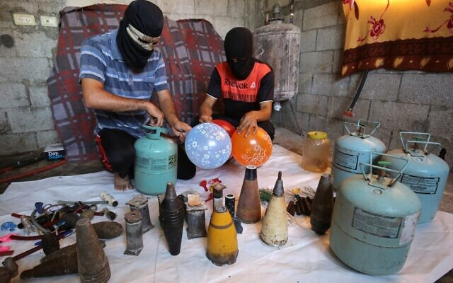 Masked Palestinians inflate balloons before attaching flammable objects to them to be flown toward Israel, in Rafah in the southern Gaza Strip, on August 8, 2020. (SAID KHATIB / AFP)