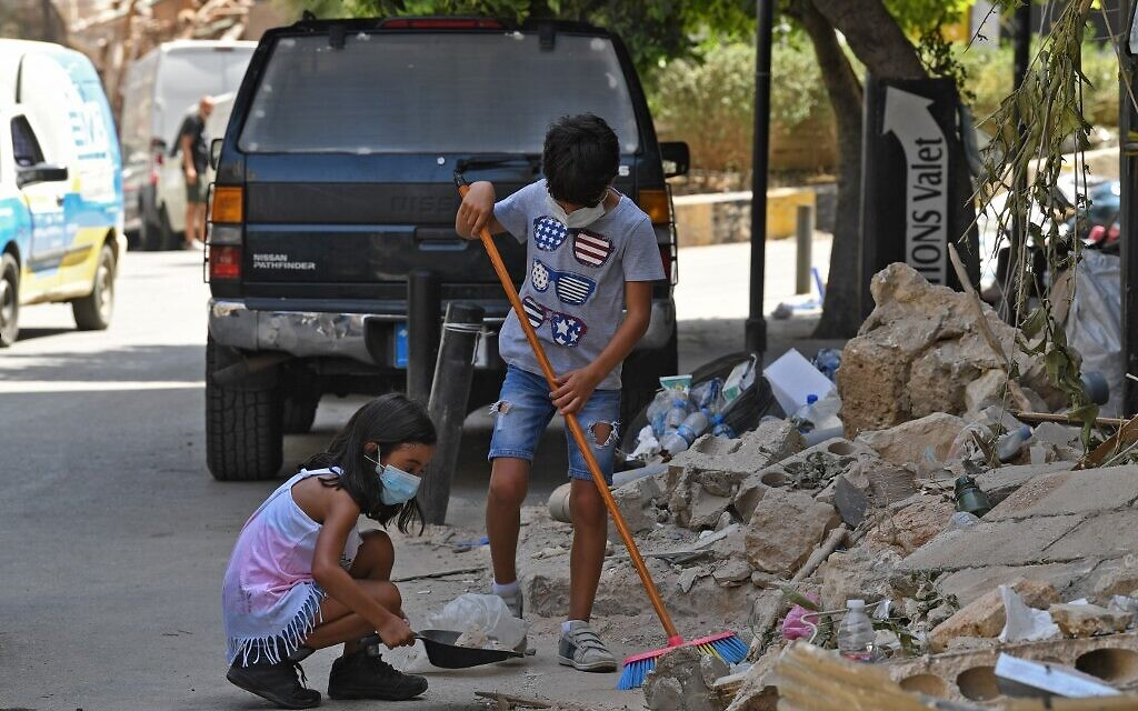 Lebanese children clean debris in Beirut's Gemmayzeh neighborhood on August 8, 2020, four days after a monster explosion killed more than 150 people and disfigured the Lebanese capital. (AFP)