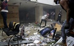 Lebanese protesters destroy the interior of the headquarters of the Lebanese association of banks in downtown Beirut on August 8, 2020, following a demonstration against a political leadership they blame for a monster explosion that killed more than 150 people and disfigured the capital Beirut. (Photo by ANWAR AMRO / AFP)