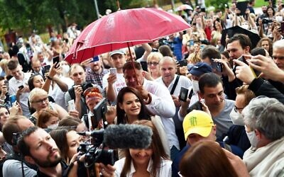 People surround presidential candidate Svetlana Tikhanovskaya as she arrives to cast her vote at a polling station during the presidential election in Minsk on August 9, 2020. (Sergei Gapon/AFP)
