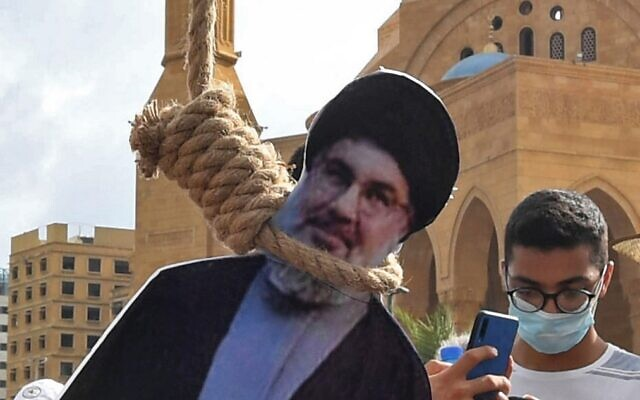 A cardboard cutout of Hassan Nasrallah, the leader of Lebanon's Hezbollah terror group, is hung in a noose by Lebanese protesters in downtown Beirut on August 8, 2020, during a demonstration against a political leadership they blame for a monster explosion that killed more than 150 people and disfigured the capital Beirut. (AFP)
