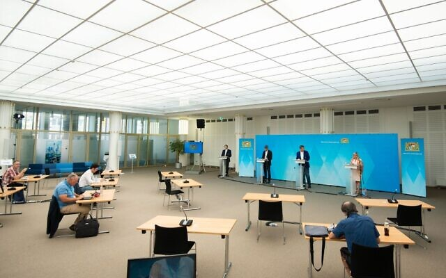 Journalists keep their distance as per coronavirus pandemic regulations while they take notes during a press conference, after a video conference of the Bavarian Cabinet at the Bavarian State Ministry of Finance and Homeland Affairs in Nuremberg, Germany, on August 10, 2020. (Nicolas Armer/Pool/AFP)