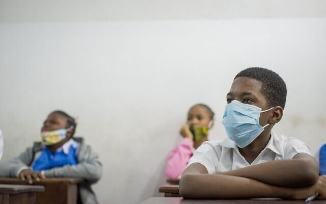 Pupils wear face masks in their classroom at the Reverend Kim school, Lingwala site, in Kinshasa, in the Democratic Republic of the Congo, on August 10, 2020, upon the resumption of classes after the COVID-19 coronavirus lockdown. (Arsene Mpiana/AFP)