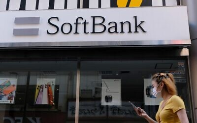 A woman walks past a SoftBank mobile store in Tokyo on August 11, 2020 (Kazuhiro NOGI / AFP)