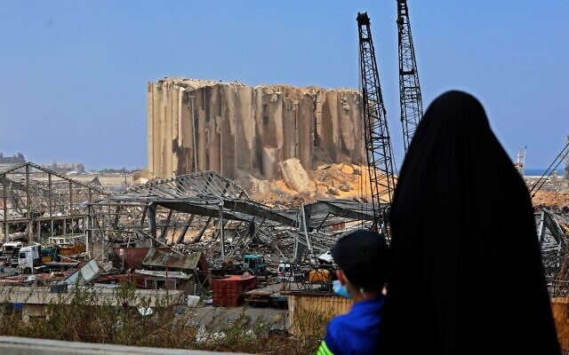A woman and her son look at the damaged grain silos at the port of Beirut following a huge explosion that disfigured the Lebanese capital, August 12, 2020. (Anwar AMRO / AFP)