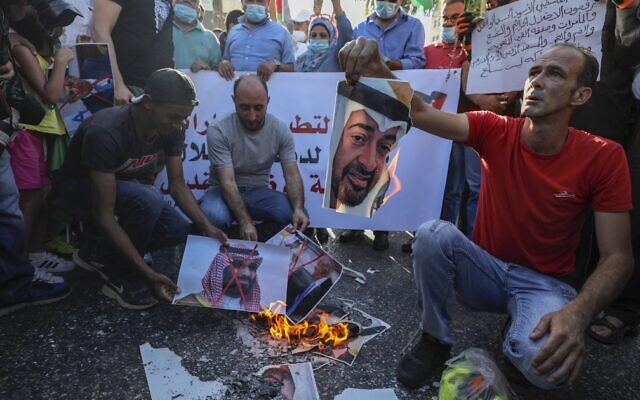 Palestinians in the West Bank city of Ramallah burn pictures of Emirati Crown Prince Sheikh Mohammed bin Zayed Al Nahyan (top) and Saudi Crown Prince Mohammed bin Salman, during a demonstration against the UAE-Israeli agreement to normalize diplomatic ties, August 15, 2020. (Abbas Momani/AFP)