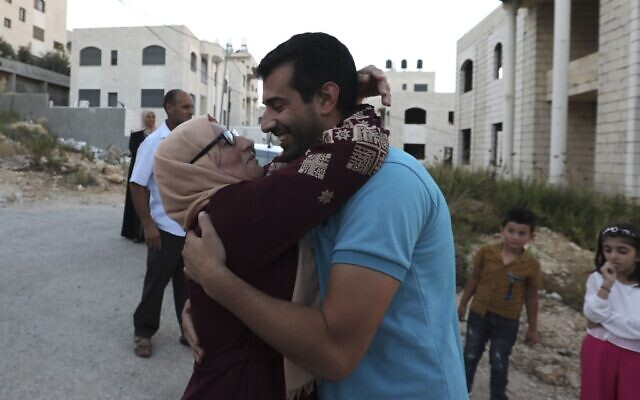 Relatives of Mahmoud Nawajaa, coordinator of the Boycott, Divestment and Sanctions (BDS) movement in the West Bank and Gaza, receive him after he was released from an Israeli prison, on August 17, 2020. (ABBAS MOMANI / AFP)