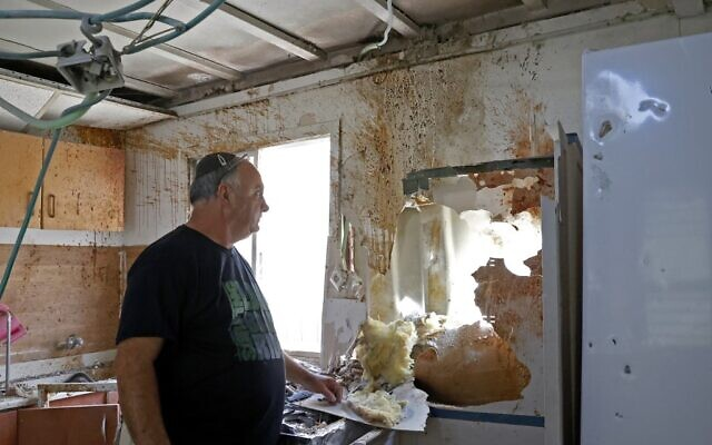Shlomo Malka in his Sderot home damaged after a rocket was  launched from the Gaza Strip, August 21, 2020 (JACK GUEZ / AFP)