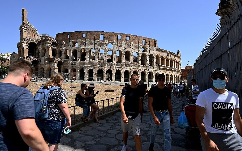 Tourists, some wearing a face mask, walk outside the Colosseum monument on August 22, 2020 in Rome during the COVID-19 infection, caused by the novel coronavirus.  (Vincenzo PINTO / AFP)