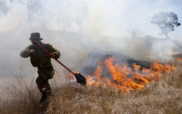 An Israeli soldier battles a blaze close to the southern kibbutz of Nir Am that was apparently caused by a balloon-borne incendiary device launched from the Gaza Strip, August 23, 2020. (Menahem Kahana/AFP)
