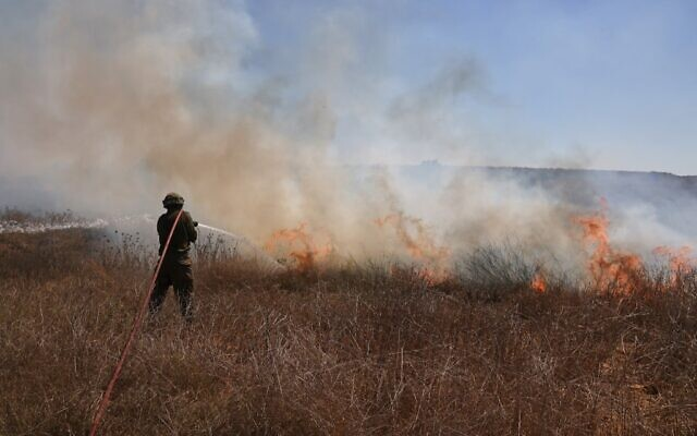 An Israeli soldier extinguishes a fire in a field close to the southern kibbutz of Nir Am, near the border with the Gaza Strip on August 25, 2020, after it was set off by incendiary balloons launched from the Palestinian enclave. (Menahem KAHANA / AFP)