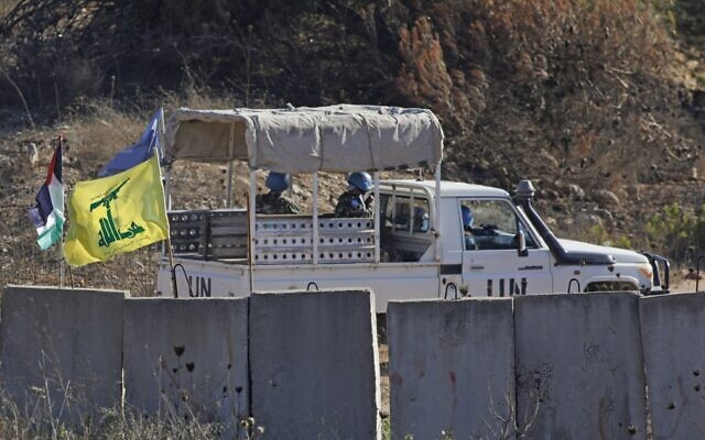 A picture taken from Kibbutz Manara shows UNIFIL peacekeepers driving past Hezbollah and Palestinian flags as they patrol along the border with Israel in the southern Lebanese village of Houla, August 26, 2020. (Jalaa Marey/AFP)