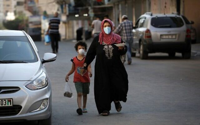 A Palestinian woman carries a plate of food as she walks alongside her child, both clad in masks, in Gaza City on August 28, 2020, during a lockdown in the Palestinian enclave due to increasing cases of COVID-19 infections. (Mohammed Abed/AFP)