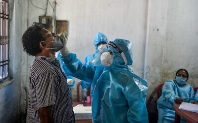 A health worker (C) collects a swab sample from a man for Rapid Antigen Test (RAT) for the COVID-19 coronavirus at a testing center in Siliguri, India, on August 29, 2020. (DIPTENDU DUTTA / AFP)