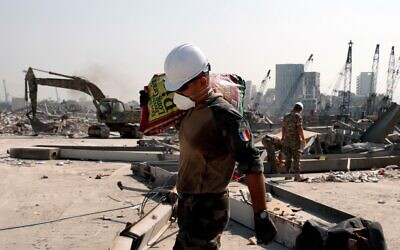 A French soldier carries a bag of rice as French forces aid the Lebanese army's work at the damaged site of the massive blast in Beirut's port area, in Beirut on August 31, 2020. (Gonzalo Fuentes/Pool/AFP)